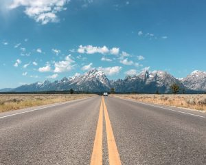 A car driving through Grand Teton National Park things to bring on a road trip